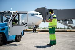 Male worker controlling airplane while colleague sitting in the car royalty free stock image
