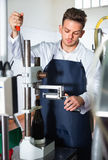 Male worker corking wine bottles with machine at sparkling wine Stock Photos