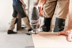 Male worker cuts the laminate Board with an electrofret saw. installing new wooden laminate flooring. concept of repair royalty free stock image