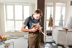 Male worker cuts the laminate Board. installing new wooden laminate flooring. concept of repair in house. stock photography