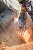 Male worker cutting bricks with angle grinder power tool, dust and debris. On construction site Royalty Free Stock Images