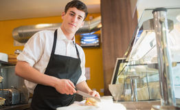 Male worker cutting sandwich on counter. Low angle view of male worker cutting sandwich on counter in bakery Royalty Free Stock Photography