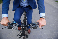 Male worker cycling in city. Close up of businessman riding a bicycle on road. Focus on his arms Stock Images