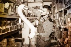 Male worker deciding on flexible ventilation pipe in workshop. Smiling male worker deciding on flexible ventilation pipe in workshop Royalty Free Stock Image
