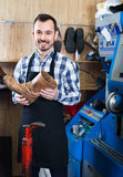 Male worker demonstrating repaired shoes in shoe. Smiling  friendly  male worker demonstrating repaired shoes in shoe repair workshop Royalty Free Stock Images