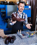 Male worker demonstrating repaired shoes in shoe. Smiling glad  male worker demonstrating repaired shoes in shoe repair workshop Royalty Free Stock Photo