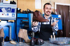 Male worker demonstrating repaired shoes in shoe. Young  friendly  male worker demonstrating repaired shoes in shoe repair workshop Royalty Free Stock Photo