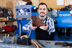 Male worker demonstrating repaired shoes in shoe. Young glad friendly  male worker demonstrating repaired shoes in shoe repair workshop Stock Image