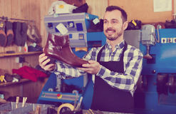 Male worker demonstrating repaired shoes in shoe. Young male worker demonstrating repaired shoes in shoe repair workshop Royalty Free Stock Photo
