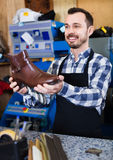 Male worker demonstrating repaired shoes in shoe. Young smiling glad friendly  male worker demonstrating repaired shoes in shoe repair workshop Stock Image