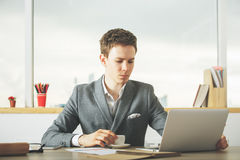 Male worker drinking coffee using laptop. Attractive caucasian male worker drinking coffee and using laptop in modern office with blurry city view and items on Royalty Free Stock Photo