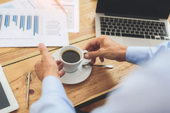 Male worker drinking hot beverage. Close up of businessman hands holding cup of coffee under working desk Royalty Free Stock Photos