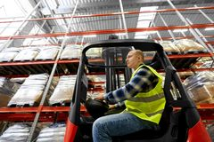 Male worker driving forklift loader at warehouse. Logistic business, shipment and people concept - male worker driving forklift loader at warehouse Royalty Free Stock Images