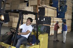 Male Worker Driving Forktruck With People In The Background. Happy male worker driving forktruck in warehouse with people having conversation in the background Stock Image