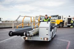 Male Worker Driving Luggage Conveyor Truck On Airport Runway. Confident young male worker driving luggage conveyor truck on airport runway Royalty Free Stock Photography