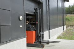 Male worker driving out of a warehouse on the fork-lift-truck Stock Image
