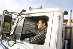 Male Worker Driving Truck. Portrait of mature male worker driving truck Royalty Free Stock Photo