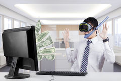 Male worker earns money with computer. Young worker wearing goggles and snorkel in the office, looking at the money on the monitor Royalty Free Stock Image