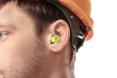 Male worker with earplug on white background. Hearing protection equipment Royalty Free Stock Image