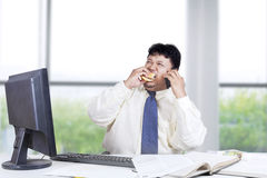 Male worker eating burger in the office. Overweight person in business suit, working in the office while eating burger and speaking on the phone Royalty Free Stock Photos
