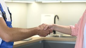 Male worker and female customer shaking hands after ending repair, good service stock footage