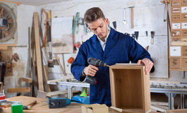 Male worker  finishing to drill drawer. Young  cheerful positive male worker  finishing to drill drawer at workshop Stock Photo