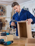 Male worker  finishing to drill drawer. Young glad  male worker  finishing to drill drawer at workshop Stock Image