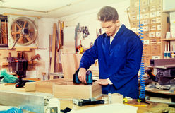 Male worker  finishing to drill drawer. Young male worker  finishing to drill drawer at workshop Royalty Free Stock Photos