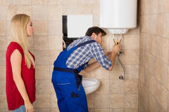 Male Worker Fixing Electric Boiler With Screwdriver. Young Woman Looking At Male Worker Fixing Electric Boiler With Screwdriver At Bathroom Stock Photo