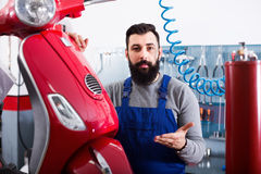 Male worker fixing failed  motorcycle in workshop Royalty Free Stock Image