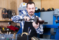 Male worker fixing failed shoes in shoe repair workshop. Adult spanish  male worker fixing failed shoes in shoe repair workshop Stock Photo