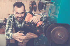 Male worker fixing failed shoes in shoe repair workshop Royalty Free Stock Photos