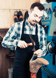 Male worker fixing failed shoes in shoe repair workshop. Smiling germany male worker fixing failed shoes in shoe repair workshop Stock Photos