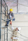 Male worker giving drill to woman on scaffold at construction site Royalty Free Stock Photography