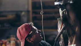 Male worker with glasses and red cap on at mechanical hangar adjusts something on metal construction with a hammer. stock video footage