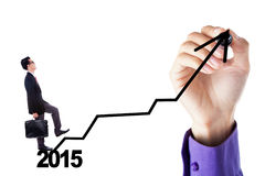 Male worker go up on a graph. Young businessman walking upward on a business graph with number 2015 Royalty Free Stock Photography