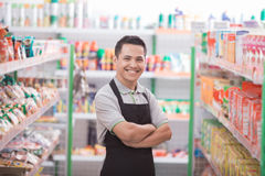 Male worker at grocery store. Asian male shopkeeper standing in front of the groceries store Stock Images