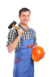 Male worker with a hammer and helmet Royalty Free Stock Photography