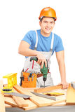 Male worker with a hand drilling machine in a workshop Royalty Free Stock Image