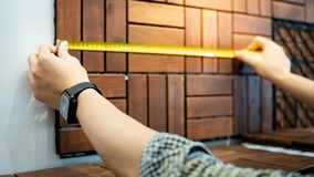 Male hand using tape measure on floor pavement. Male worker hand using tape measure for measuring dimension of wooden floor pavement block pattern mockup royalty free stock images