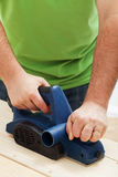 Male worker hands with electric planer. Male worker hand with electric planer - closeup Royalty Free Stock Image