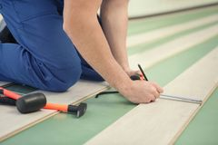 Male worker hands installing laminate. Flooring Royalty Free Stock Image