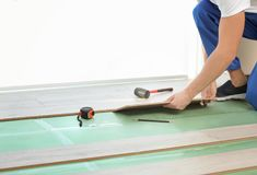 Male worker hands installing laminate. Flooring Stock Image