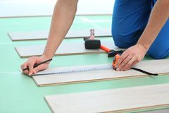Male worker hands installing laminate. Flooring Stock Photography