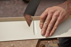 Male worker hands sawing wood board using saw. stock images
