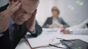 Male worker has migraine attack caused by stress and exhaustion at workplace. Stock footage stock video footage