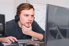 Male worker with headphones. Design Office With Workers At Desks. Program developer working at his desk. Virtual office operator. Worker looking at notebook at royalty free stock images