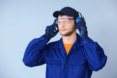 Male worker with headphones. On grey background. Hearing protection equipment Royalty Free Stock Photos