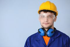 Male worker with headphones on grey background. Hearing protection equipment Royalty Free Stock Photo