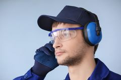 Male worker with headphones on grey background. Hearing protection equipment Stock Photo
